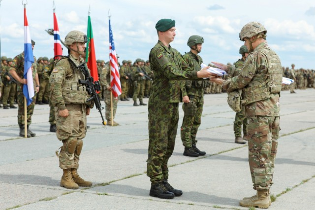 The Saber Strike 18 exercise colours are presented to Brig. Gen. Richard R. Coffman, deputy commanding general, 1st Infantry Division, during the closing ceremony at Rukla Airfield, Lithuania, June 15, 2018. 18,000 participants from 19 allied and partner nations participated in the eighth iteration of Saber Strike, June 3 - 15. The next iteration is scheduled for 2020.