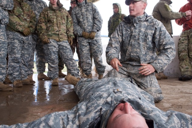 Alaska Army National Guard Staff Sgt. Stephen Behrens, Alaska Army National Guard Medical Detachment training noncommissioned officer, demonstrates how to properly use a tourniquet, June 17, 2018, to Soldiers of the 297th Regional Support Group at Five Hills Training Area, Mongolia, during Khaan Quest 2018.
