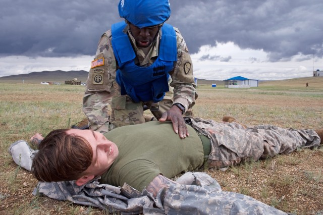 Alaska Army National Guard Spc. Jahmoi Hodge, a member of the platoon representing the 297th Regional Support Group, assesses simulated casualty U.S. Navy Hospital Corpsman 3rd Class John Bustamonte, III Marine Expeditionary Force, June 17, 2018, during Tactical Combat Casualty Care training at Five Hills Training Area, Mongolia, as part of Khaan Quest 2018.