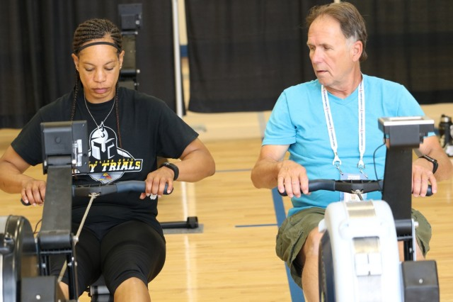 "U.S. Army Staff Sgt. Altermese Kendrick listens closely to indoor rowing coach Robert Hurley during indoor rowing training, May 30, at the U.S. Air Force Academy Cadet Center Gymnasium, during the 2018 Department of Defense Warrior Games. Kendrick finished in third place for the ""Ultimate Champion title during the games. The DoD Warrior Games were conducted from June 1 - 9. It is an adaptive sports competition for wounded, ill and injured service members and veterans. Approximately 300 athletes representing teams from the Army, Marine Corps, Navy, Air Force, Special Operations Command, United Kingdom Armed Forces, Canadian Armed Forces, and the Australian Defence Force competed in archery, cycling, track, field, shooting, sitting volleyball, swimming, wheelchair basketball, powerlifting and indoor rowing. (U.S. Army photo by Robert Whetstone)"