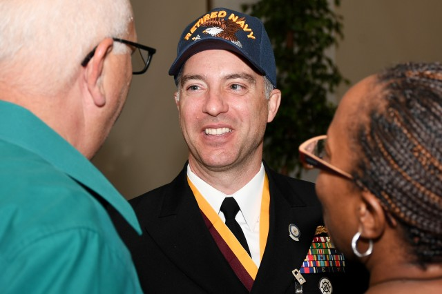 "Retired Navy Cmdr. Jason Brianas sports a ""Retired Navy"" ball cap during a reception that followed his retirement ceremony at Scott Air Force Base, Illinois June 7.  Brianas served 21 years in the Navy, culminating with a joint assignment at the Military Service Deployment and Distribution Command (SDDC)."
