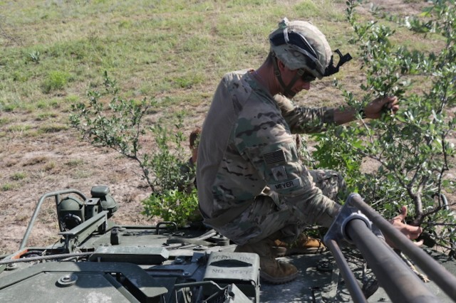 Sgt. Ethan Meyer, 3rd Cavalry Regiment, Fort Hood, Texas, applies branches to the Stryker, June 5, 2018.  Staff Sgt. Christopher Darensbourg, 3CR, said that applying camouflage to the Strykers is a lost art. (U.S. Army photo by Sgt. Melissa N. Lessard)