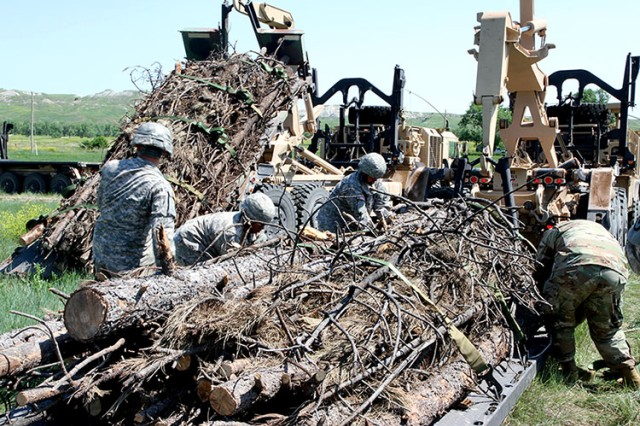 Soldiers from the 137th Transportation Company, Kansas Army National Guard, loosen straps on a load of timber at Red Shirt, S.D., June 15, 2018. The M1057 A1 Palletized Loading System carries the timber from Custer, S.D., to Native American reservations during the annual timber haul operation as part of the Golden Coyote training exercise.