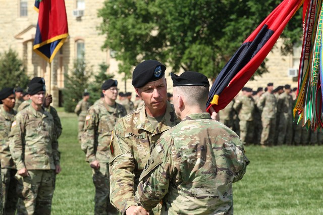 Maj. Gen. Joseph M. Martin, 1st Infantry Division and Fort Riley outgoing commanding general, passes the 1st Inf. Div. colors to Gen. Robert B. Abrams, U.S. Army Forces Command senior leader, during the division's change of command ceremony at the Cavalry Parade Field, Fort Riley, Kansas, June 8. The passing of the colors signifies the end of Martin's responsibilities as the commanding general of the 1st Inf. Div. (Chad L. Simon, 1st Inf. Div. Public Affairs)