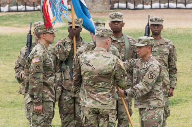 Lt. Col. Paul Oh, the outgoing commander of the 304th Military Intelligence Battalion, passes the battalion colors to Col. Brian Lieb, Commander of the 111th Military Intelligence Brigade, during a Change of Command Ceremony on Brown Parade Field, Fort Huachuca June 15.