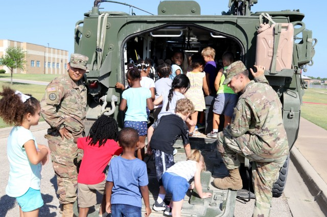 "Soldiers with Ironhawk Troop, 3rd Squadron ""Thunder,"" 3rd Cavalry Regiment, allow children to explore the inside of a Stryker vehicle during the Harker Heights Library Big Truck show June 6, 2018, at Harker Heights, Fort Hood, Texas."