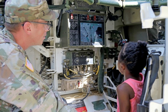 "Staff Sgt. Nikkholai Miller an infantryman with Ironhawk Troop, 3rd Squadron ""Thunder,"" 3rd Cavalry Regiment, allows children from the community to operate a camera on a Stryker vehicle during the Harker Heights Library Big Truck show June 6, 2018, at Harker Heights, Fort Hood, Texas."