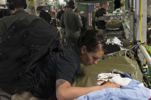 Capt. Argelia Felix-Camacho, a critical care nurse at the U.S. Army Institute of Surgical Research Burn Center and member of the USAISR Burn Center Burn Flight Team comforts a patient in Guatemala before a flight to the Shriner's Hospital for Children in Galveston, Texas.