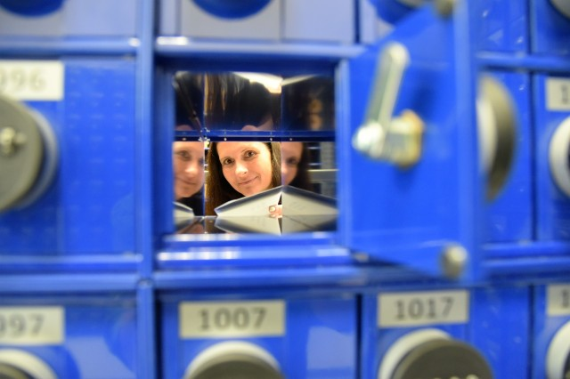 Postal Operations Specialist Anja Jung, places a letter in a mail receptacle at the new Landstuhl Army Post Office.