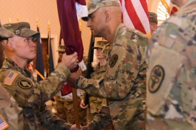 Col. Patrick A. Donahue (left), the newly assigned commander of Public Health Command-Atlantic, passes the unit colors to PHC-A Command Sgt. Maj. Elvin Medina during the change-of-command ceremony on June 7 at Club Meade.