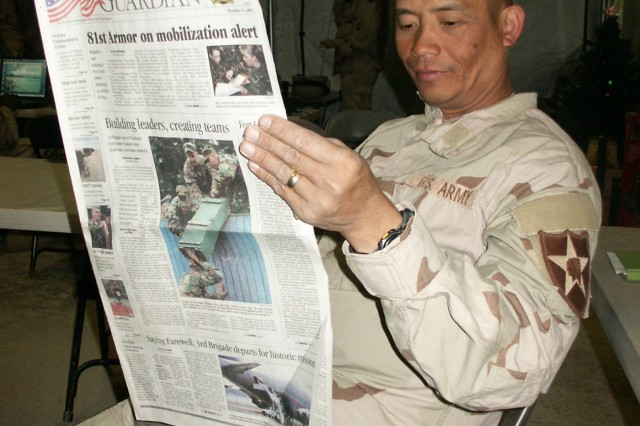 Command Sgt. Maj. Jeffrey Du reads the Northwest Guardian newspaper while taking a break in the brigade's tactical operations center in 2003. The brigade was part of Task Force Ironhorse, conducting operations north of Baghdad.