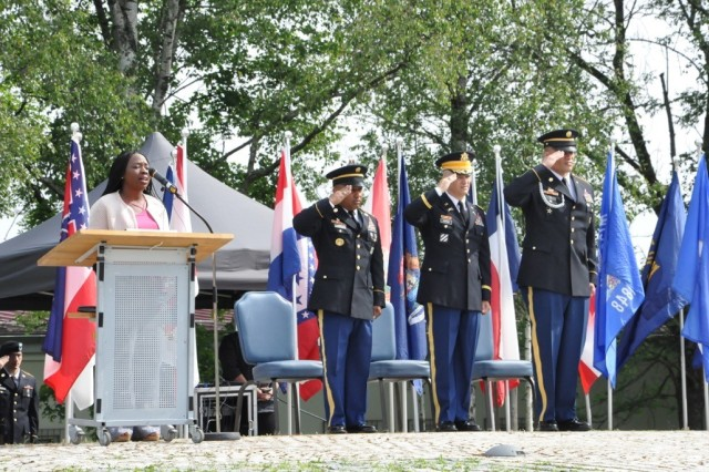 Tess Moss-Beaman sings a heartfelt rendition of the Star Spangled Banner as Command Sgt. Maj. Mariano Z. Alvarez, Col. Neal Corson and Command Sgt. Maj. Toese Tia salute during the change of responsibility ceremony, June 15.