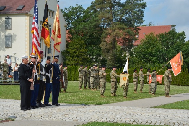 A joint service/national color guard and troops on the field salute the national anthems of Germany and the United States, June 15.