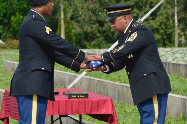 Command Sgt. Maj. Mariano Z. Alvarez accepts an American flag as part of his retirement ceremony, June 15.