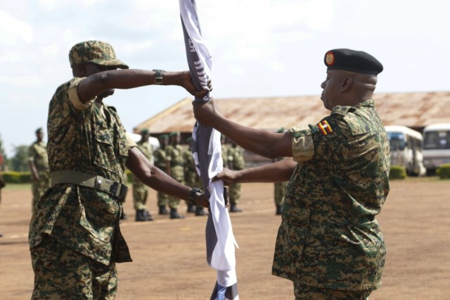Photo By Spc. Angelica Gardner | Uganda People's Defence Force (UPDF) Brig. Gen. James Ruhesi (left), exercise JA18 UPDF co-director, passes the exercise flag over to another UPDF soldier to signify the commencement of Justified Accord 2018, Jinja, Uganda, June 23, 2018. Justified Accord is a two-week combined and joint exercise designed to demonstrate the capacity and capability of participants in peacekeeping operations and employing the African Union Mission in Somalia procedures
