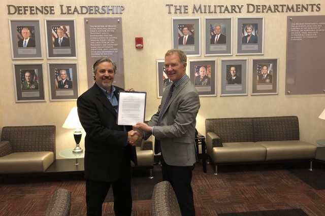 Craig A. Spisak, left, the Army DACM, and Professor John T. Dillard, Col., USA (Ret.), NPS senior lecturer in systems acquisition management and technical representative for the new curricula, hold the memorandum of agreement signed by Lt. Gen. Paul A. Ostrowski and NPS President Ronald A. Route, Vice Adm. USN (Ret.), on May 18 at the Pentagon. The memorandum cements a partnership to provide relevant education to the Army's military and civilian acquisition workforce.