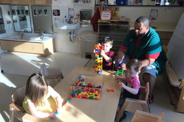 Russell Morton, a child and youth services assistant at Cody Child Development Center, helps children towers. The CDC reopened Monday after being closed for three days last week.