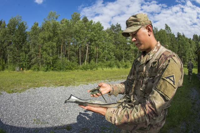U.S. Army Staff Sgt. Cesar Gonzalez 1st Battalion, 4th Infantry Regiment, Joint Multinational Readiness Center, 7th Army Training Command (7ATC), shoots an azimuth to orient his map during the 7ATC Best Warrior Competition June 19, 2018 at Grafenwoehr Training Area, Germany. Skeps, a Palmyra, VA native is competing in the three-day event ending June 21 with the announcement of the 7ATC Officer, Noncommissioned Officer and Soldier of the Year. The winners will move on to compete in the U.S. Army Europe Best Warrior Competition. (U.S. Army Photo by Kevin S. Abel)