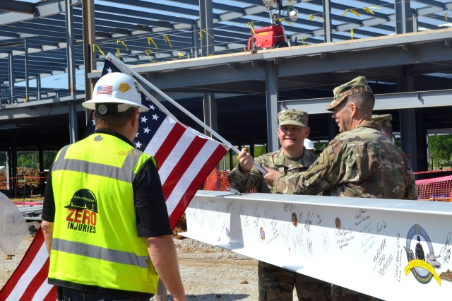 Brig. Gen John Evans Jr., the commanding general for U.S. Army Cadet Command and Fort Knox; Maj. Gen. Todd McCaffrey, commanding general 1st Army Division East and Maj. Gen. Ray Royalty, commanding general of the 84th Training Command attached the U.S. flag to the final beam that was later attached to the building. The beam had already been signed, unit coins affixed and a Fort Knox centennial logo stamped on it.