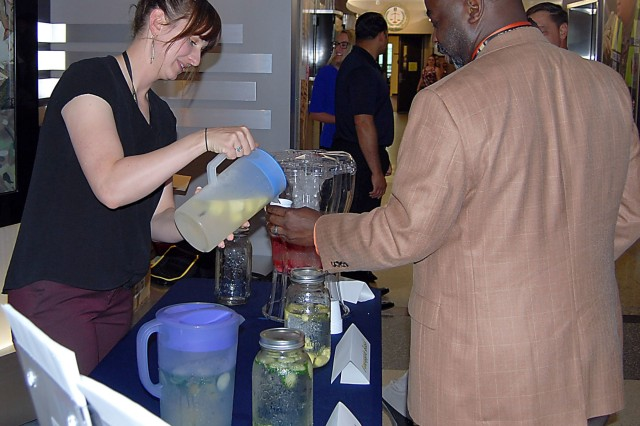 Lauren Biswell of ASC's Readiness Division pours some infused water for Raphael Garrison during a kickoff event for the 10-Day Water Reset Challenge held June 20 at Rock Island Arsenal, Illinois.  The event was moved indoors to the foyer of Building 390 due to threatening weather. (Photo by Paul Levesque, ASC Public Affairs)