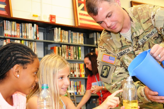 Then-CW4 Blake Leibach, C Co., 1-212th Avn. Regt., gives a hand to Aniya Tuner and Alyssa Hansen, military family members, during the Fizzy Chemistry Mad Scientist Workshop at the Center Library last year.