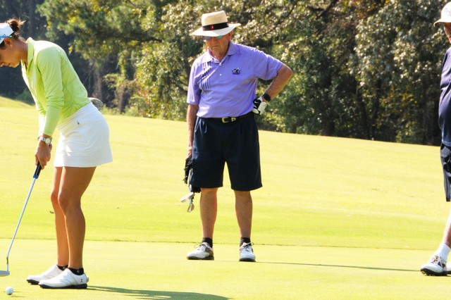Madison Opfer, LPGA professional, lines up her putt as her teammates, Richard Hutson and Armand Millette, retired military participants, look on during the SWGC Pro-Am tournament last year.