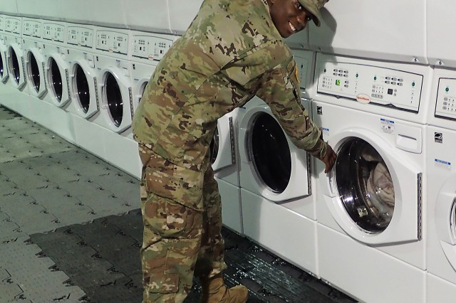 A Soldier with the 4th Infantry Division Sustainment Brigade uses the new LOGCAP self-service laundry facility featuring 40 washers/dryers at Roosevelt Roads base camp in Puerto Rico, Oct. 27. The self-service laundry, open 24 hours daily, features heating and cooling, high-efficiency short-cycle time units. LOGCAP provided this and many other essential services to personnel supporting relief efforts resulting from Hurricane Maria. (Photo by Rick Birkhead, LOGCAP Support Contractor).