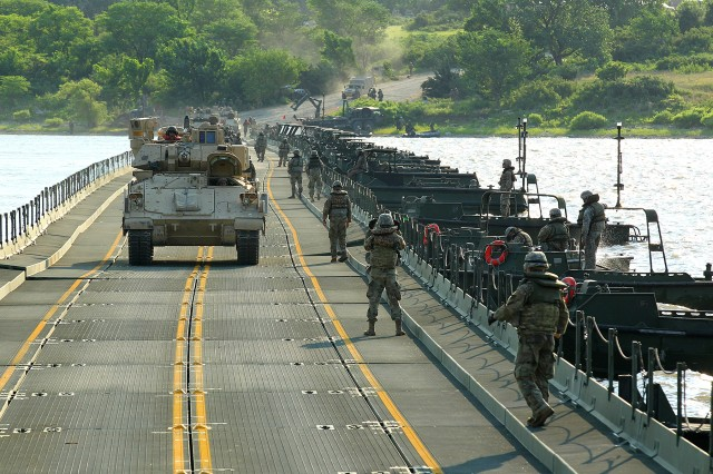 A Bradley Fighting Vehicle with 1st Battalion, 16th Infantry Regiment, 1st Armored Brigade Combat Team, 1st Infantry Division, crosses a temporary, floating bridge at Milford Lake, Kansas, June 15 during training exercise Gauntlet. The 600-meter bridge was constructed by three active-duty Mobile-Role Bridge Companies from throughout the U.S. and a National Guard MRBC from Louisiana. (Chad L. Simon, 1st Inf. Div. Public Affairs)