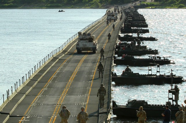 Bradley Fighting Vehicles and M1A2 Abrams tanks with 1st Battalion, 16th Infantry Regiment, 1st Armored Brigade Combat Team, 1st Infantry Division, cross a temporary, floating bridge at Milford Lake, Kansas, June 15 during training exercise Gauntlet. The 600-meter bridge was constructed by three active-duty Mobile-Role Bridge Companies from throughout the U.S. and a National Guard MRBC from Louisiana. (Chad L. Simon, 1st Inf. Div. Public Affairs)