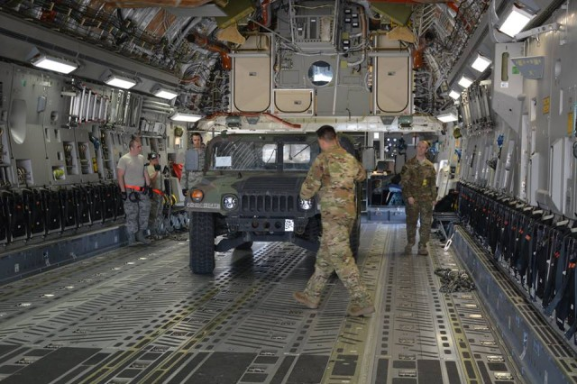 Airmen from the 7th Airlift Squadron, 62nd Airlift Wing, and Soldiers from 8th Squadron, 1st U.S. Cavalry, 2nd Stryker Brigade Combat Team, 2nd Infantry Division, guide a Humvee aboard a C-17 aircraft before departure to Fort Hunter-Liggett, California during a Joint Deployment Readiness Exercise, Rainier Warrior 18 at Joint Base Lewis-McChord, Wash., June 6, 2018.