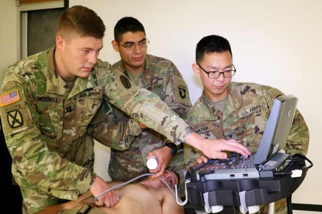 Interservice Physician Assistant Program Phase II student Capt. Dakota Mitchell, assigned to Blanchfield, shows combat medic specialist, Spc. Joshua Huante, assigned to 1st Battalion, 187th Infantry Regiment, 3rd Brigade Combat Team, 101st Airborne Division, and patient administration specialist, Spc. Wooyoung Chun, assigned to 626th Brigade Support Battalion, 3rd Brigade Combat Team, 101st Airborne Division how to operate an ultrasound machine on fellow IPAP Phase II student Capt. Zachary Quigg. IPAP Phase II students are assigned to Blanchfield for 13 months to complete clinical rotations. They provide medic training at noon the second Wednesday of the month at the hospital for medics and interested medical personnel on post. The medic training helps the Phase II students learn how they will run a training program in their battalion after completing Phase II training and graduating from the IPAP program. U.S. Army photo by Maria Yager.