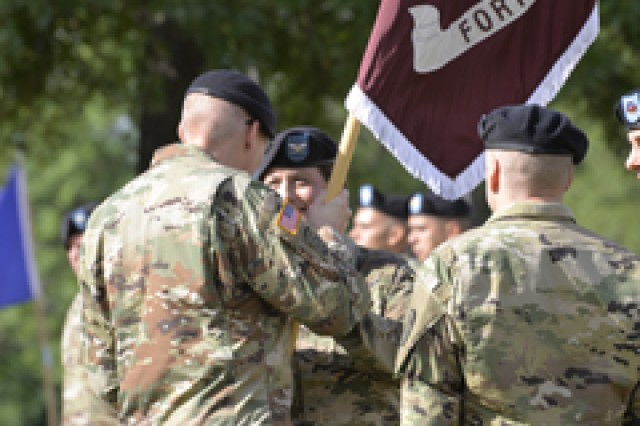 Brig. Gen. Jeffrey Johnson, Regional Health Command-Central commanding general, passes the Medical Department Activity colors to Col. Kimberlie Biever June 22.