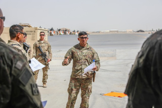 First Sgt. Branden Velazquez, senior enlisted leader for Alpha Company, 1st Battalion, 12th Infantry Regiment, 2nd Infantry Brigade Combat Team, 4th Infantry Division, instructs Soldiers from 1st Bn., 12th Inf. Reg. on safety procedures before conducting medical evacuation training, June 9, 2018, in Kandahar Airfield, Afghanistan. Velazquez has built a 12-year career out of imparting his contributions to the 2IBCT's history. (U.S. Army photo by 1st Lt. Christopher Locklier/2IBCT UPAR)