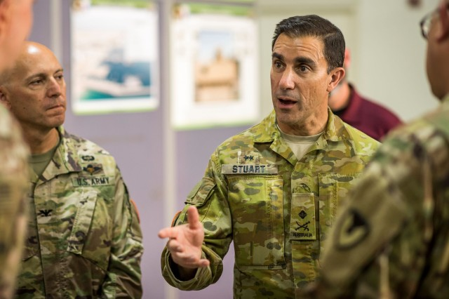 Australian Army Maj. Gen. Simon Stuart, Multinational Force and Observers Force Commander, asks questions during a tour of an Army Prepositioned Stocks-5 warehouse at Camp Arifjan, Kuwait, June 23. (U.S. Army photo by Kevin Fleming, 401st AFSB Public Affairs)