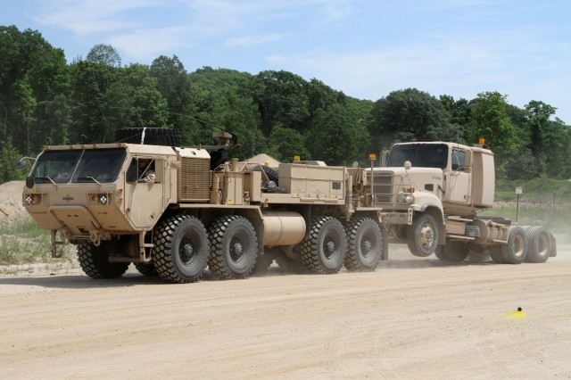 A Heavy Expanded Mobility Tactical Truck (HEMTT) A4 wrecker with the 211th Maintenance Company out of Newark, Ohio tows a M915A5 Truck Tractor with the 1487th Transportation Company out of Piqua, Ohio while completing tactical convoy operations training June 21, 2018 at the Camp Grayling Joint Maneuver Training Center in Grayling, Mich.