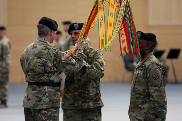 U.S. Army Maj. Gen. John Baker, commanding general of U.S. Army Network Enterprise Technology Command, passes the 2d Theater Signal Brigade colors to incoming commander Col. Neil Khatod during an assumption of command ceremony June 26, 2018 in Wiesbaden, Germany.