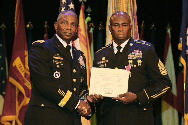 Lt. Gen. Darrell K. Williams, director, Defense Logistics Agency, presents Command Sgt. Maj. Nathaniel J. Bartee with a certificate of appreciation from the commander in chief during the Combined Arms Support Command Change of Responsibility and Retirement Ceremony June 20 at the Lee Theater. Bartee served as Williams' top enlisted Soldier for the last two assignments of his career.