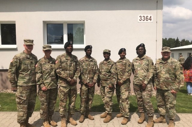 Col. Richard A. Wholey Jr. (left), Spc. Hope Martin (second from left) and Command Sgt. Maj. Anthony Collins (far right) congratulate members of the 678th ADA BDE and the 5-7 ADA BN, upon graduation of BLC, Grafenwoehr, Germany, June 15, 2018.