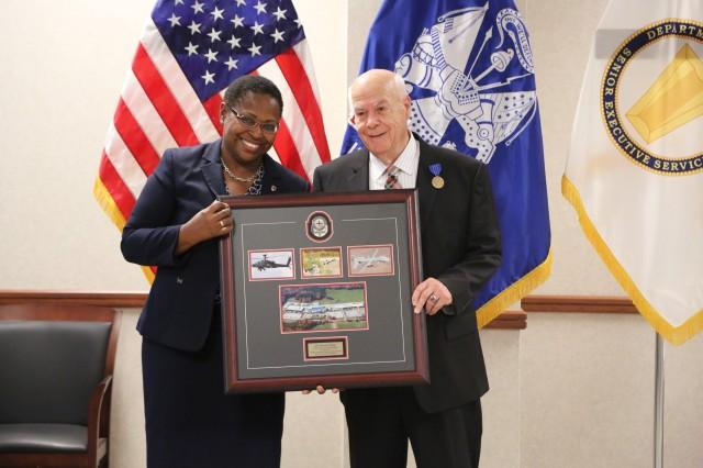 AMRDEC Director Dr. Juanita Harris presents a memento to Dr. Bill Craig during his retirement ceremony June 25.