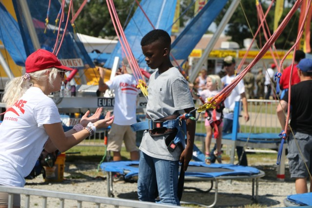 FORT BENNING, Ga. (June 26, 2018) - An assistant helps a child into the holster on one of the festival attractions. The Maneuver Center of Excellence and Fort Benning opened its gates to the community June 23, 2018, in celebration of the Independence of the United States. (U.S. Army Photo by Markeith Horace, Maneuver Center of Excellence Public Affairs Photographer)
