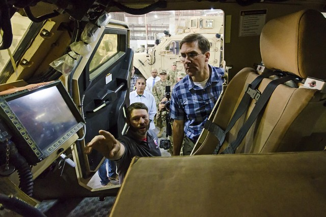 """Don Mallette (left), logistics management specialist, Army Field Support Battalion-Kuwait, shows Secretary of the Army Mark Esper the inside of a """"Configured for Combat"""" Mine-Resistant Ambush Protected (MRAP) vehicle during a tour of Army Prepositioned Stocks-5 facilities at Camp Arifjan, Kuwait, June 21, 2018."""