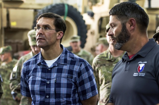 "Secretary of the Army Mark T. Esper (left) looks at ""Configured for Combat"" equipment during a tour of Army Prepositioned Stocks-5 facilities at Camp Arifjan, Kuwait, June 21, 2018."