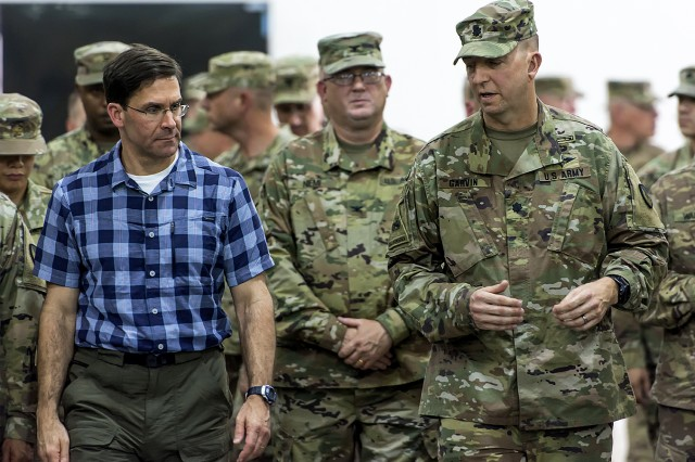 """Lt. Col. Christopher Garvin (right), commander, Army Field Support Battalion-Kuwait talks to Secretary of the Army Mark T. Esper about """"Configured for Combat"""" equipment during a tour of Army Prepositioned Stocks-5 facilities at Camp Arifjan, Kuwait, June 21, 2018."""