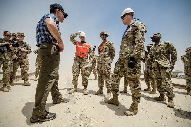Secretary of the Army Mark T. Esper (left) speaks with Soldiers at a remote vehicle staging lot during a tour of Army Prepositioned Stocks-5 facilities at Camp Arifjan, Kuwait, June 21, 2018.