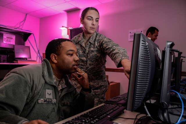Airman 1st Class Tevin Miller and Airman 1st Class Amanda Button, 707th Communications Squadron client system technicians, update software for computers that will be used on Air Force networks in January at Fort Meade, Maryland. Joint forces, coordinating from command centers to the warfighter in the field, will use integrated software systems that allow for early warning and situational understanding. The Analytical Framework's goal is to get capabilities like these into the hands of warfighters sooner.