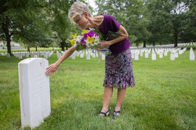 Judi Boyer-Bouchard touches the headstone for her brother, Sgt. 1st Class Alan Boyer, during a visit to Arlington National Cemetery, Va., June 20, 2018. The remains of Boyer, who was missing in action for 48 years, were eventually recovered and identified by the Defense POW/MIA Accounting Agency in 2016.