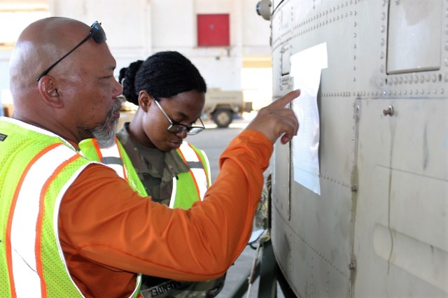 Traffic management specialist Frank Viray and cargo specialist Spc. Nashelle Mendez check the lading numbers on helicopters at Kalaeloa Airfield on June 11.