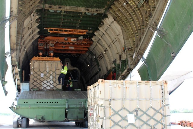AN-124 crew members use the airplane's internal gantry crane to load containers on June 14.