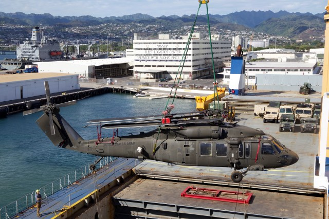The forward ship's crane of the M/V Ocean Jazz offloads a UH-60 Black Hawk helicopter from the ship's hold on June 18.