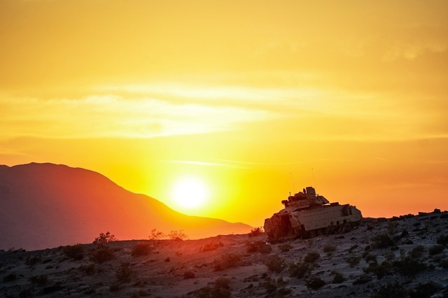 A Bradley Fighting Vehicle climbs the side of Mount Tiefort Mountain in Fort Irwin, California at sunset in preparation for a training mission during rotation 18-08 the National Training Center May 27-June 17, 2018.